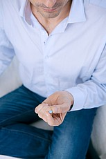A man holding a blue pill for erectile dysfunction